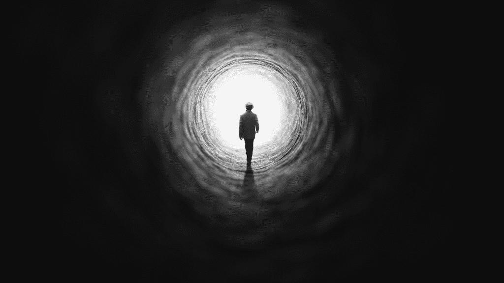 Silhueta de pessoa na caverna caminhando em direção a luz