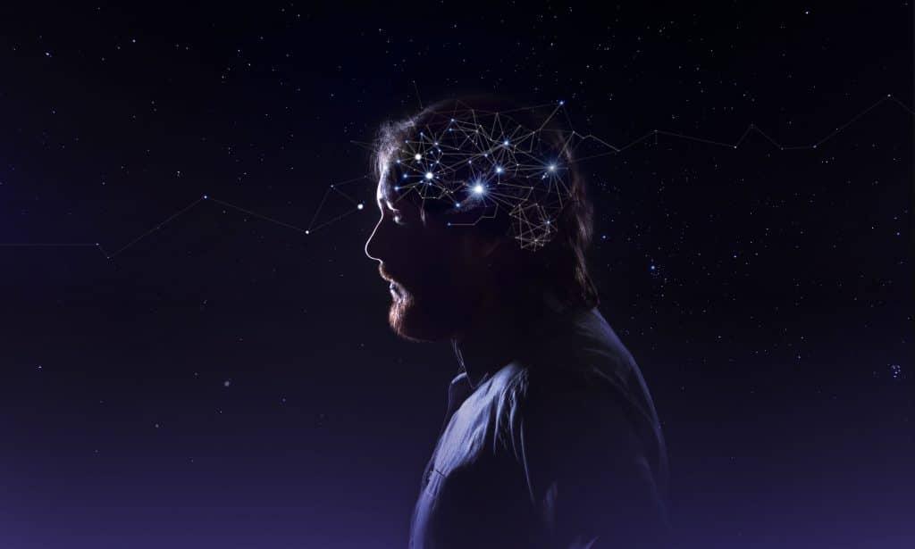Homem de perfil em frente a um céu estrelado. A área de seu cérebro está se fundindo com o céu, graças a pontos de luz representando neurônios e que se misturam com as estrelas do céu.