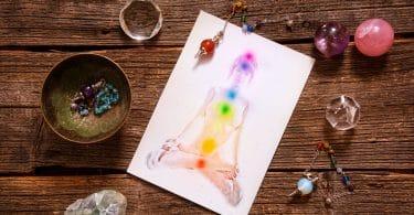 Chakras desenhado em um corpo de uma pessoa co pedras ao redor da mesa