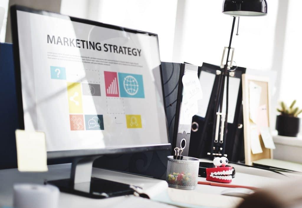 Computador ligando em uma teça com estratégias de marketing