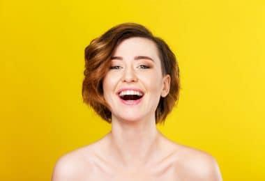 Mulher de cabelos curtos vista de frente, sorrindo.