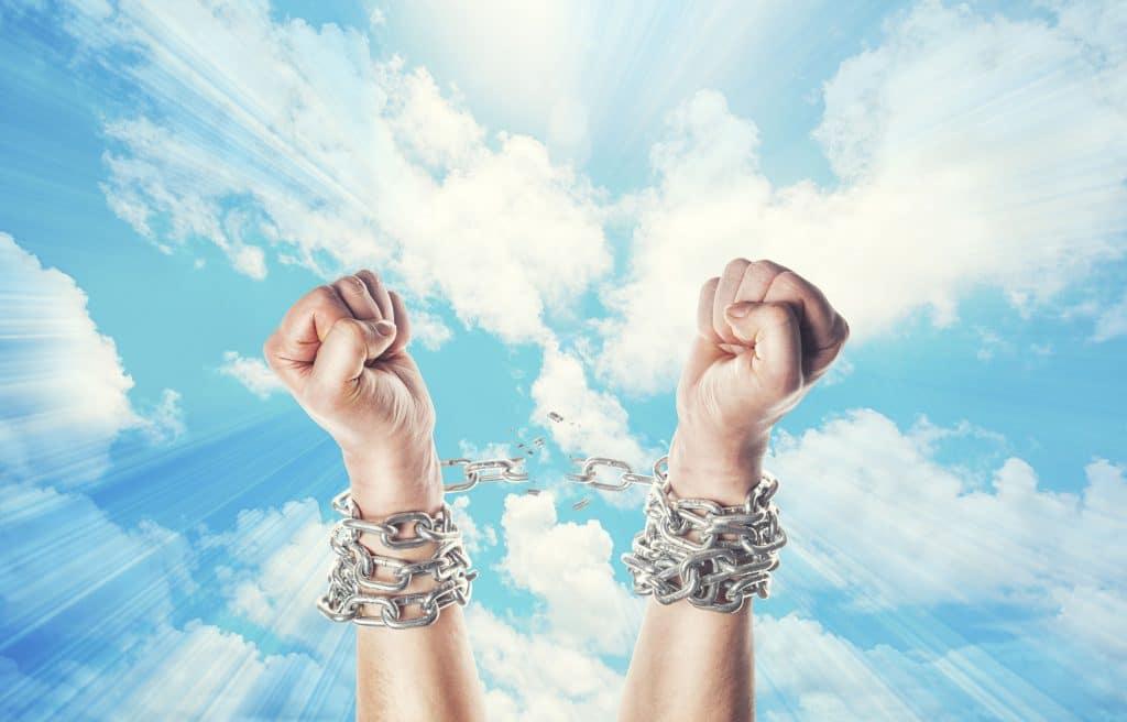 Duas mãos levantadas, com um céu azul ao fundo. Os pulsos estão com correntes enroladas, mas o elo entre eles no centro está se rompendo.