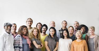 Grupo de pessoas de diferentes idades, cores e etnias, lado a lado e sorrindo.