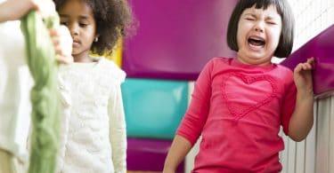 Menina pequena chorando com a boca aberta, enquanto outra menina de mesmo tamanho ao seu lado mantém a compostura e olha para o chão.