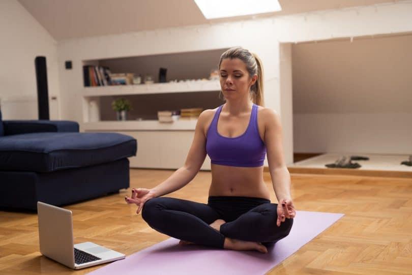Mulher sentada em posição de meditação em frente a um computador.
