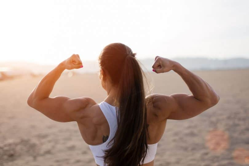 Mulher de costas em praia, usando uma camiseta regata, flexionando seus músculos com os braços virados para cima.
