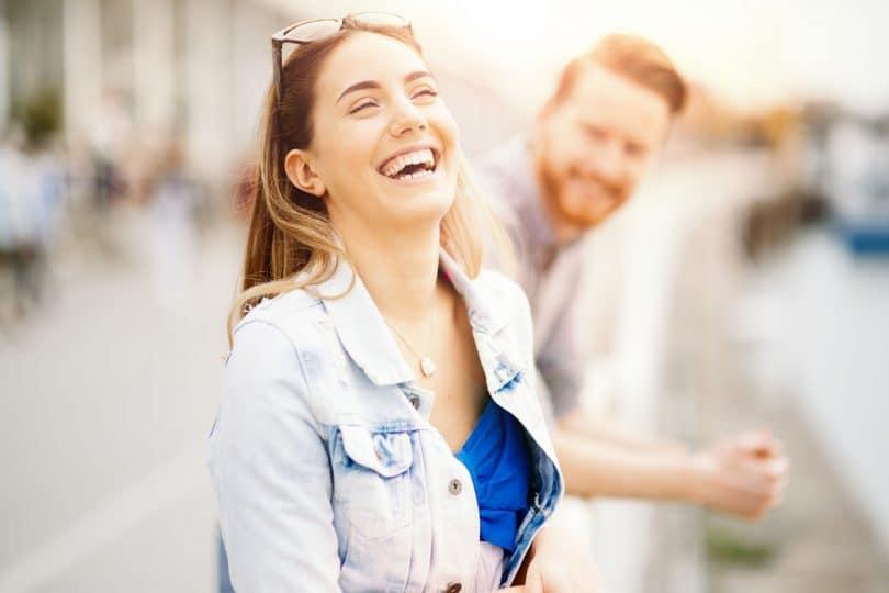 Mulher sorrindo na rua com um homem ao seu lado.