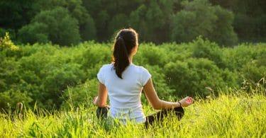 Mulher meditando em gramado no alto de montanha