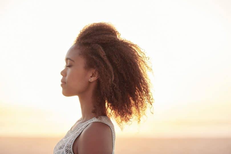 Mulher de cabelos cacheados vista de perfil, com os olhos fechados e expressão calma, em frente à praia.