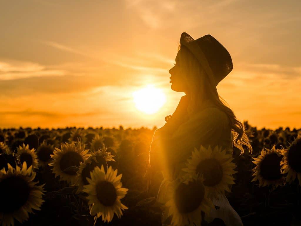 Mulher em um campo de girassóis pensativa