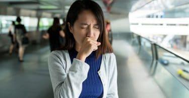 Mulher em local público, tossindo com os olhos fechados e a mão direita na frente de sua boca.