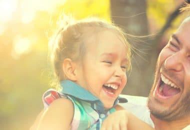 Menina criança e homem adulto rindo em um parque durante o dia.
