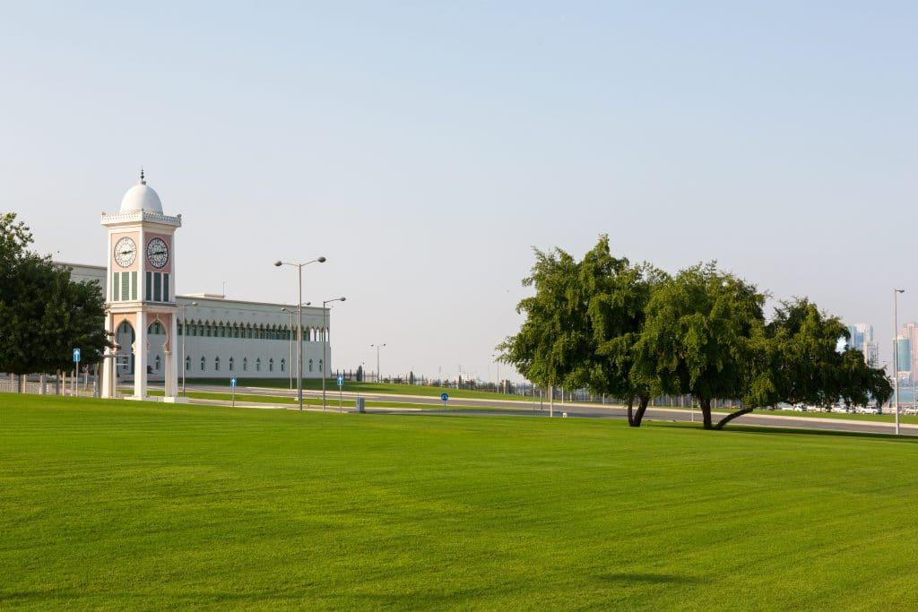 Lindo parque na cidade do Katar com gramado bem verde e uma estrondosa árvore ao centro. Ao fundo uma torre com um lindo relógio.