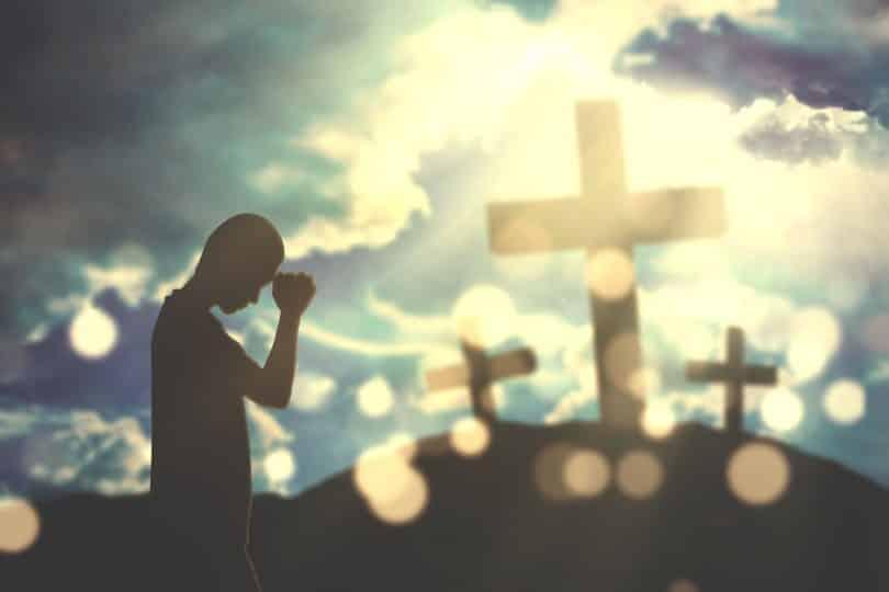 Um homem adora a Deus com três cruzes e luz do sol no céu.