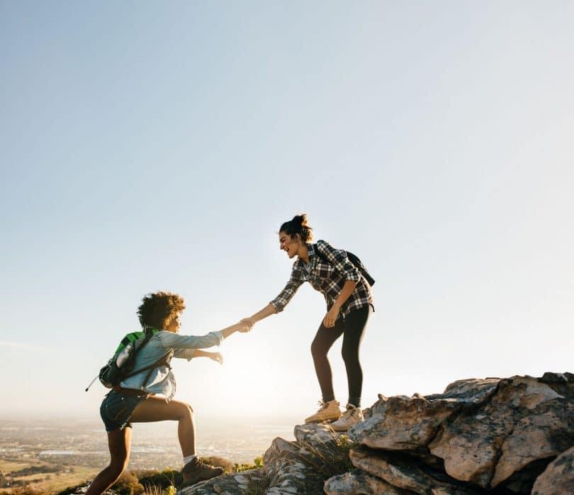 Mulher ajudando a outra a subir na montanha