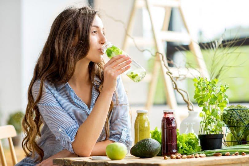 Mulher de cabelos longos e ondulados sentada em uma mesa de madeira, bebendo água aromatizada com limão e ervas. Sobre a mesa, estão vários tipos de hortaliças, sucos naturais e frutas.