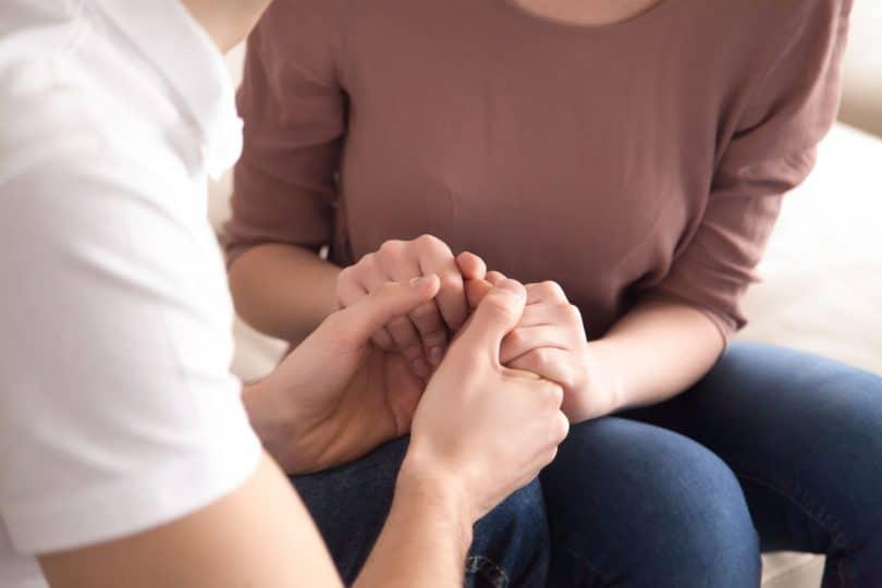 Homem segura as mãos de uma mulher enquanto os dois estão sentados em um sofá.