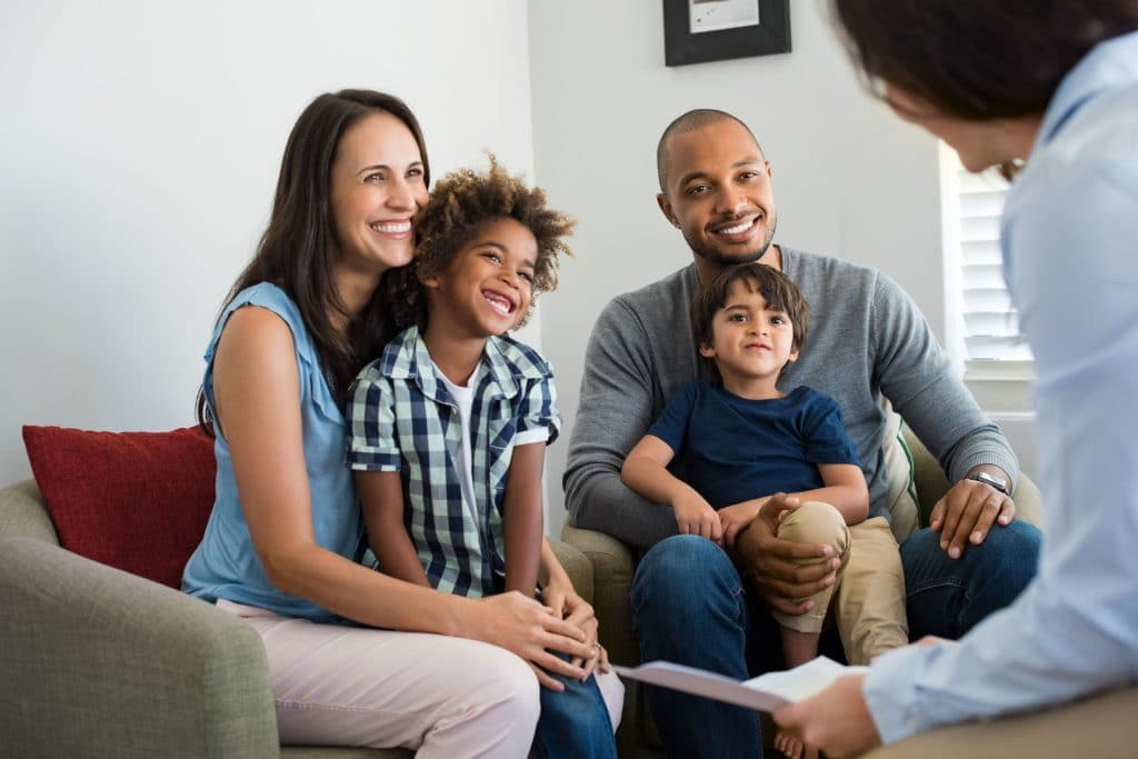 Família falando com um consultor enquanto homem e mulher seguram em seu colo crianças