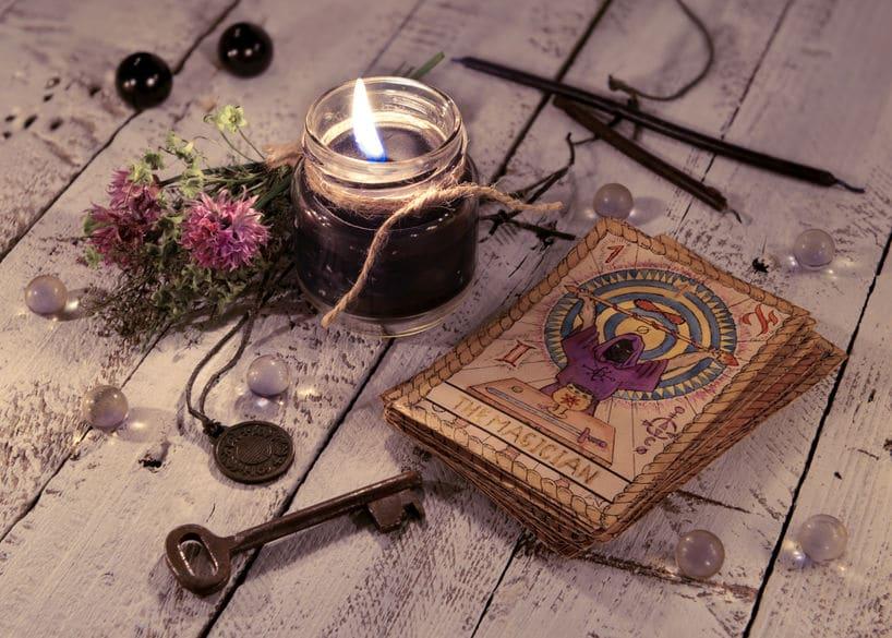 Vela preta acesa dentro de pequeno pote de vidro. Cartões de tarô em uma pilha, uma chave e pequenas bolinhas de cristal.