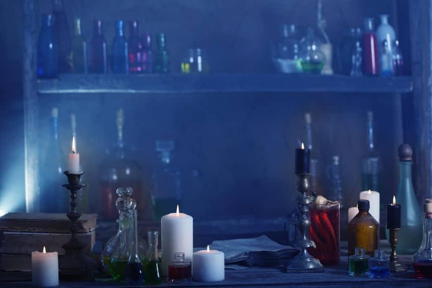 Sala escura com velas acesas, garrafas vazias, entre outros..