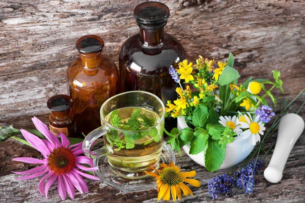 Xícara com chá e ao lado algumas flores com garrafas