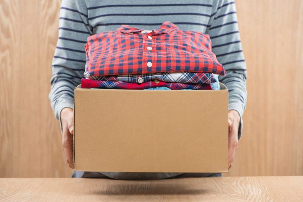 Homem segurando uma caixa com roupas para doação