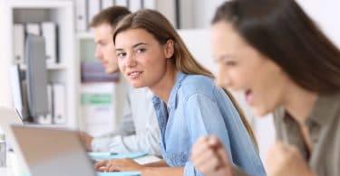 Garotas no computador e garota ao fundo em foco olhando garota da frente comemorando