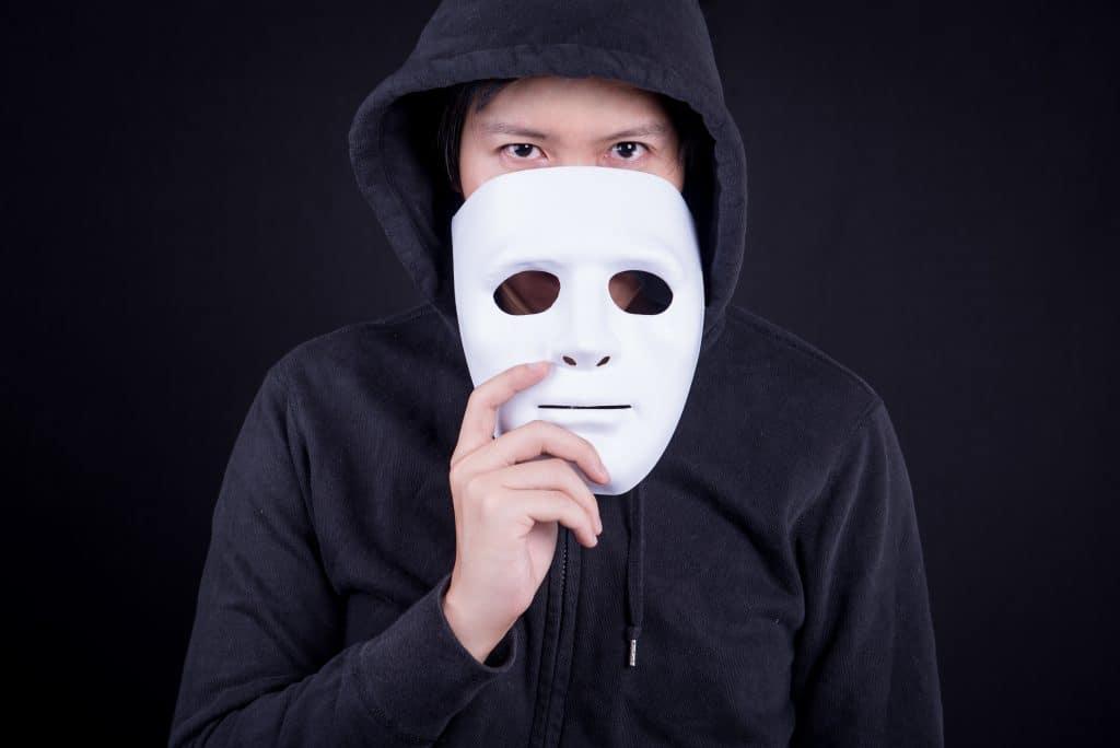 Imagem de um homem vestindo um moletom preto com capuz. Ele segura uma máscara de gesso branca em suas mãos.