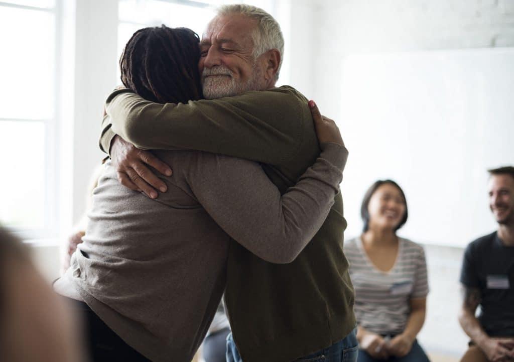 Senhor abraçando outra pessoa