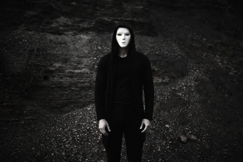 Imagem de um homem de corpo inteiro. Ele usa uma roupa preta e tem uma máscara branca sobre o seu rosto.