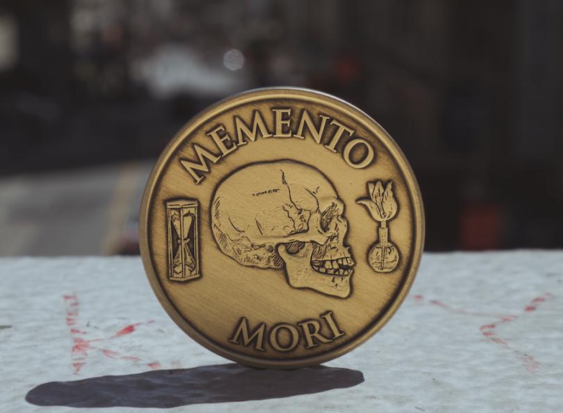 """Imagem de uma moeda apoiada verticalmente sobre uma mesa. Nela, há a gravura de uma caveira de perfil com os escritos """"memento mori""""."""