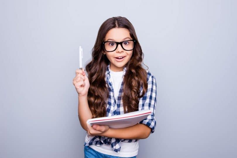 Garotinha usando óculos com caneta e caderno na mão com expressão de surpresa