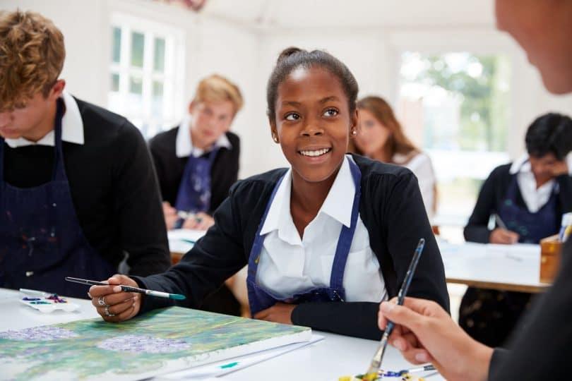 Menina adolescente sorrindo em aula de pintura na escola.