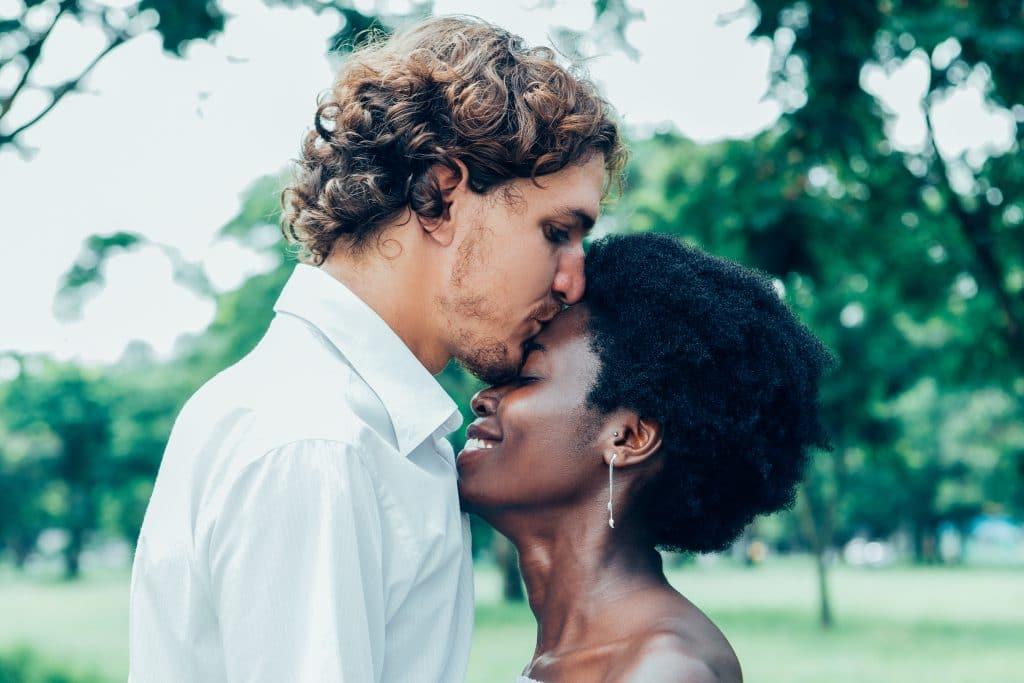 Homem louro de cabelos cacheados usando camisa branca de mangas longas. Ele está dando um beijo na testa de sua namorada negra. Ela está linda e feliz. Ambos estão em uma praça.