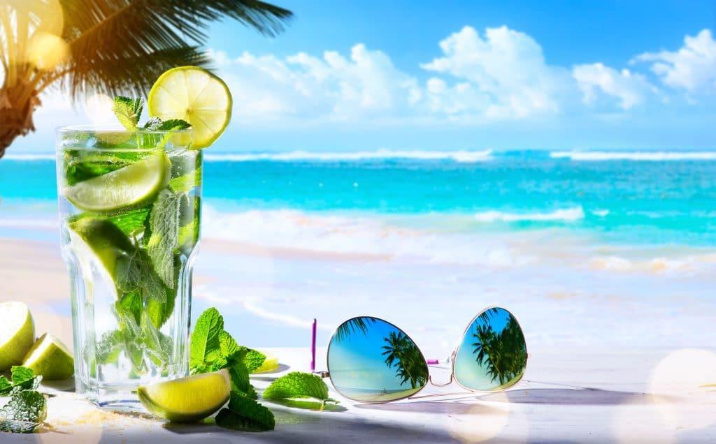 Copo com bebida transparentes em uma praia.