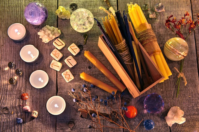 Runas, velas, flores, ervas e objetos mágicos em cima de tábuas de madeira.