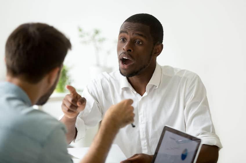 Dois homens discutindo frente a frente. Ambos estão apontando o dedo indicador para o outro.