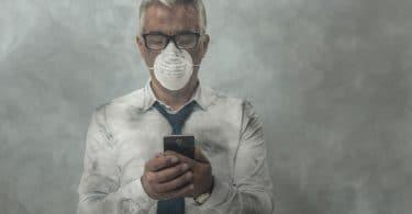 Homem mexendo no celular com máscara no rosto e fumaça ao redor
