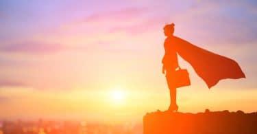Silhueta de uma mulher de perfil, com uma maleta de trabalho e uma capa de super-heroína.