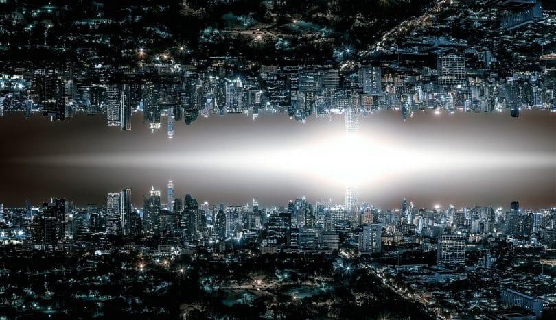 Horizonte de uma cidade grande com muitas luzes acesas em prédios e nas ruas. No centro da imagem existe uma luz em formato de losango. Na parte superior, a mesma imagem da parte de baixo mas de ponta-cabeça, como um reflexo.