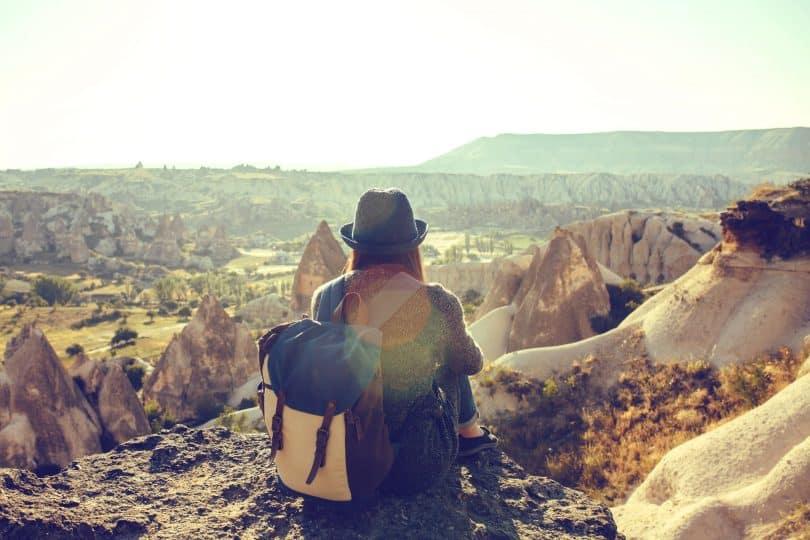Mulher sentada em uma montanha alta observando a paisagem.