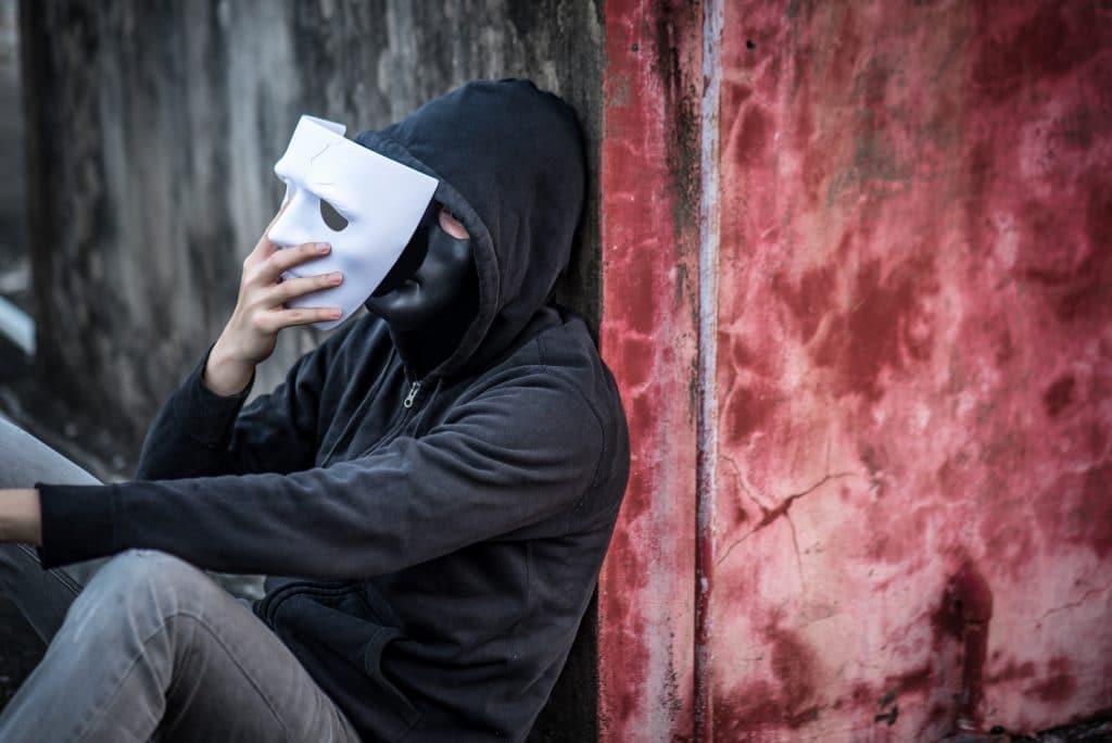 Homem vestindo um moletom preto e uma calça jeans cinza claro. Ele está sentado e encostado na parede. Ele usa em seu rosto uma máscara preta e em uma de suas mãos ele segura uma máscara branca sendo posta sobre a máscara preta.