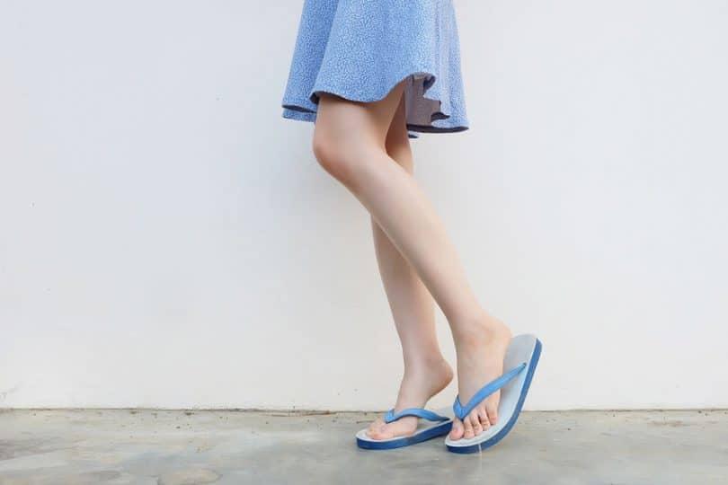 Pernas de mulher vestindo saia e chinelos de dedo em frente a uma parede. Ela está de lado e uma de suas pernas está levemente flexionada, pois está apoiando na ponta do pé.