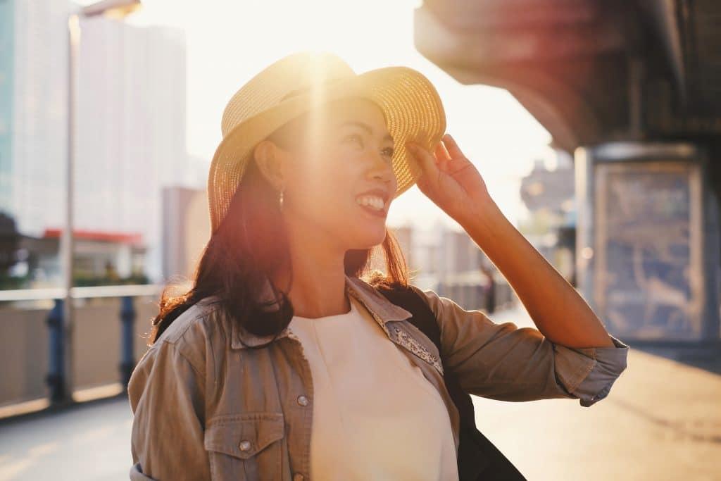 Mulher em uma rua da cidade segurando seu chapéu e sorrindo