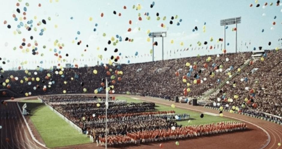 Cerimônia de abertura dos Jogos Olímpicos de Tóquio, em 1964. O interior de um estádio com as arquibancadas lotadas, o campo lotado com os atletas e diversos bexigas coloridas voando no céu.