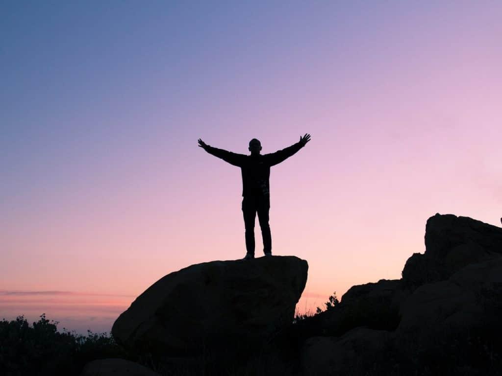 Silhueta de homem em cima de uma pedra, com os braços abertos. O céu está violeta.