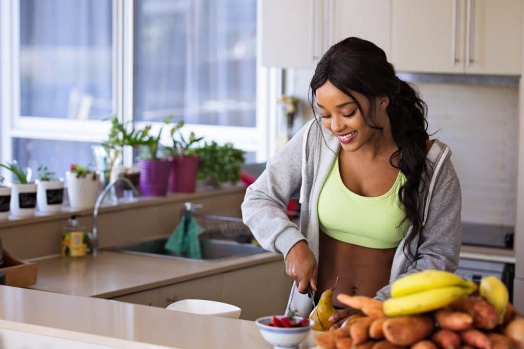 Mulher cortando uma pera com uma faca, no balcão da cozinha, enquanto sorri.