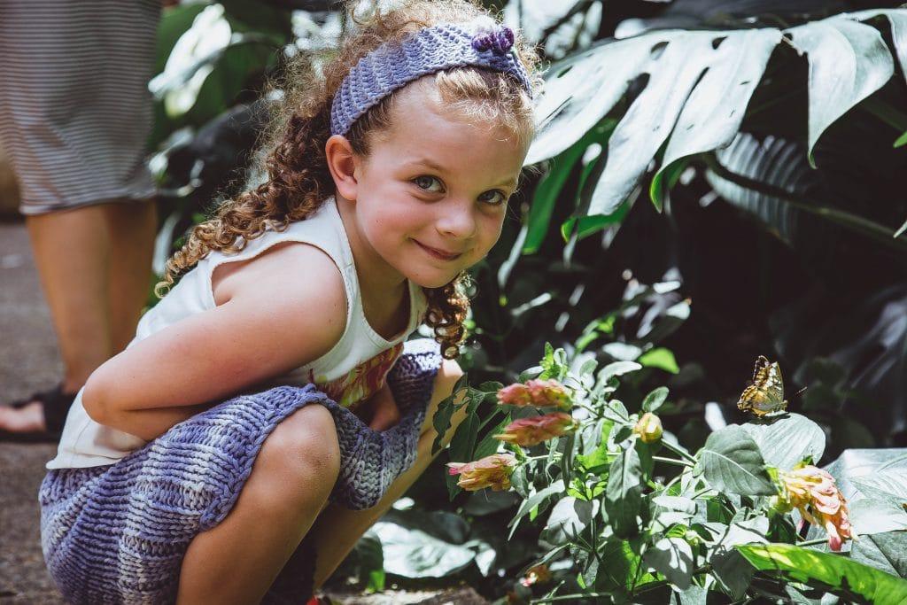 Criança  ao lado de uma flor com borbolete