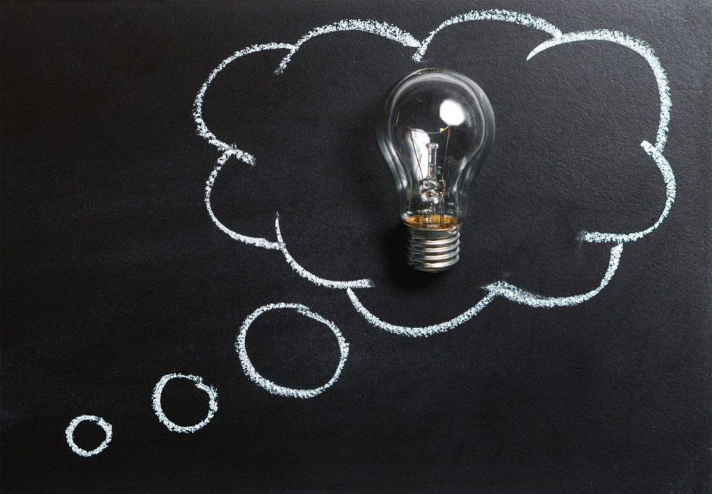 Desenho de balão de pensamento com giz branco em uma lousa preta, e uma lãmpada de verdade dentro do balão.