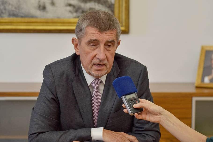 Homem vestindo terno e gravata, com os braços cruzados na frente do seu corpo, fala em um gravador que está sendo segurado por alguém que não aparece na foto.